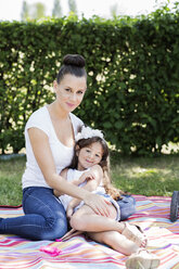 Portrait of mother and her little daughter sitting on a blanket - GDF000818