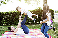Woman balancing her little son on her feet - GDF000824