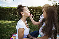 Little girl painting her mother's lips - GDF000826