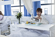 Content patient in hospital bed having lunch - ZEF006781