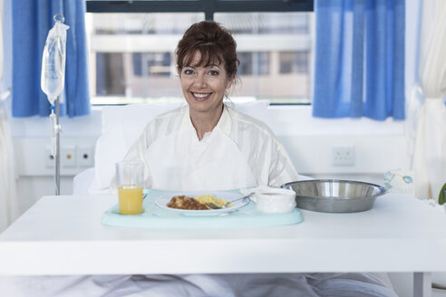 Smiling patient in hospital bed having lunch - ZEF006786