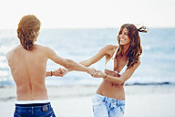 USA, Miami, happy young couple having fun on the beach - CHAF000827