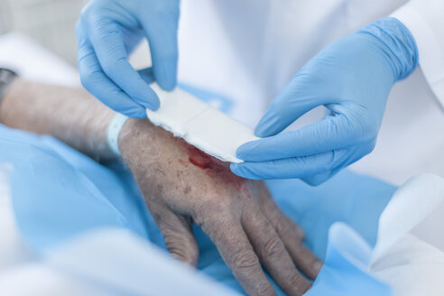 Nurse dressing a wound on patients hand - ZEF006555