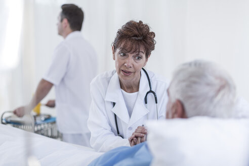 Doctor visiting senior patient in hospital bed - ZEF006832
