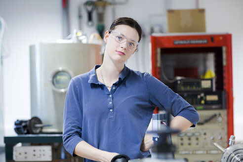 Portrait of young woman with safety goggles in workshop - SGF001776