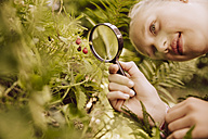 Girl looking through magnifier at small strawberries - MFF001892