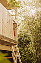 Boy looking out of a tree house - MFF001900