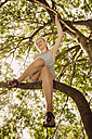 Girl sitting on a branch in tree - MFF001908