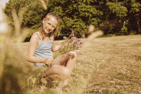 Girl picking flowers in field - MFF001911