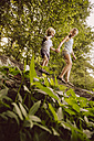 Little boy and girl balancing on fallen tree in forest - MFF001925