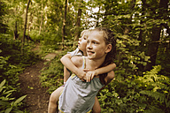 Girl carrying little boy piggyback through a forest - MFF001933