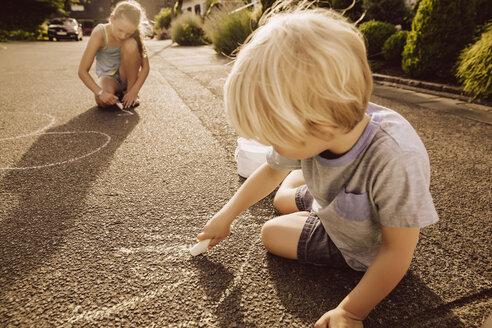 Children using sidewalk chalk in their neighborhood - MFF001942