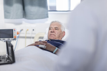 Portrait of senior man lying in a hospital bed - ZEF006251