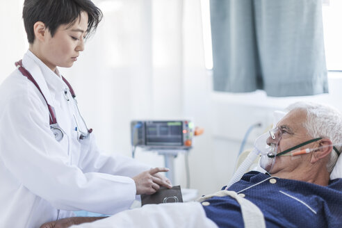 Doctor taking blood pressure of senior man with oxygen mask in a hospital - ZEF006266