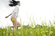 Young woman running on a meadow - BFRF001370