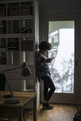 Young woman with cell phone leaning against cabinet - FKF001317