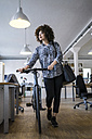 Young woman pushing bicycle in office - FKF001320