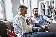 Two smiling businessmen sharing laptop - FKF001225
