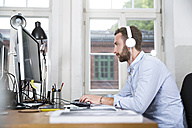 Young man in office wearing headphones working on computer - FKF001234