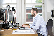 Young man in office working on computer - FKF001323