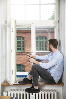 Young man with cell phone sitting at the window looking out - FKF001324