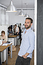 Smiling man in office with colleagues in background - FKF001328