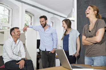 Colleagues laughing in office - FKF001334