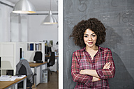 Smiling young woman standing at blackboard in office - FKF001291