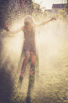 Girl having fun with splashing water in the garden - SARF002038