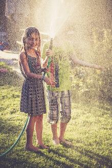 Two children splashing with water in the garden - SARF002035
