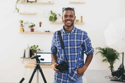 Portrait of smiling young man in his photographic studio - EBSF000771