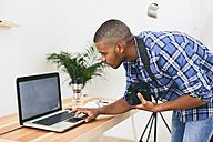 Young man working with laptop in his photographic studio - EBSF000774