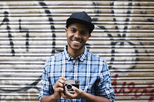 Portrait of smiling young man with baseball cap and camera in front of roller shutter - EBSF000787