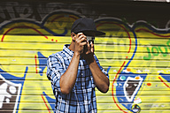 Young man with baseball cap and camera taking photos in front of roller shutter - EBSF000793