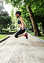 Spain, Oviedo, young woman jumping rope in the park - MGOF000318