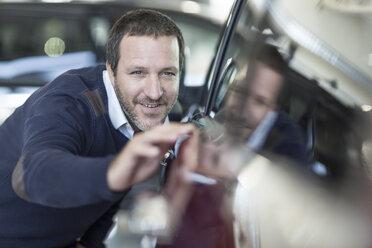 Smiling man examining new car at car dealership - ZEF006906