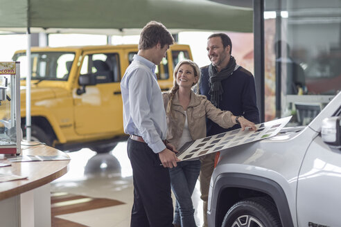 Couple choosing from color sample at car dealer - ZEF006909