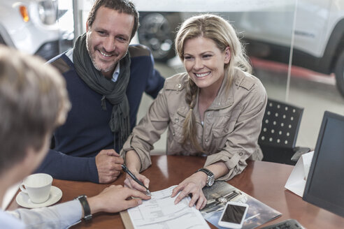 Couple signing sales contract at car dealership - ZEF006912