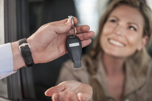 Woman sitting in new car receiving key - ZEF006915