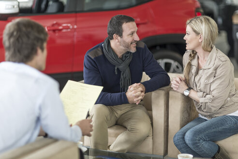Couple discussing at car dealership - ZEF006918