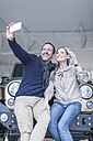 Happy couple at car dealership taking selfie in front of new car - ZEF006926