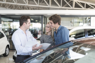 Car dealer showing brochure to young couple in showroom - ZEF006940
