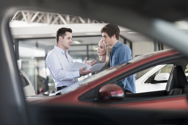 Car dealer showing brochure to young couple in showroom - ZEF006946