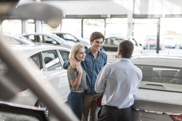 Car dealer talking to young couple in showroom - ZEF006962