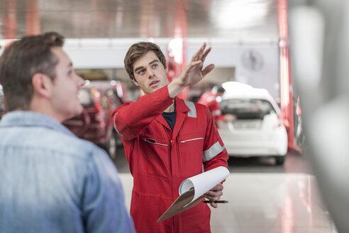 Car mechanic and customer in repair garage - ZEF006984