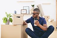 Young man sitting beside cardboard boxes having a coffee break - EBSF000803