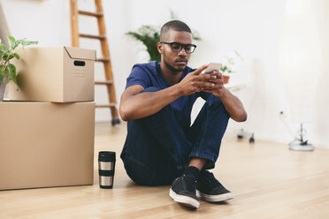 Young man sitting beside cardboard boxes having a break - EBSF000806