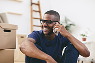 Portrait of happy young man sitting beside cardboard boxes telephoning with smartphone - EBSF000807