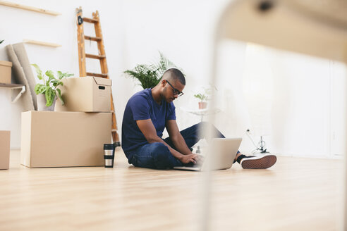 Young man sitting beside cardboard boxes in his new flat using laptop - EBSF000809