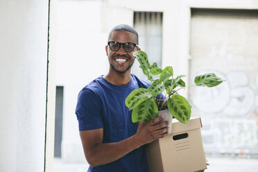 Portrait of happy young man with cardboard box and foliage plant - EBSF000814